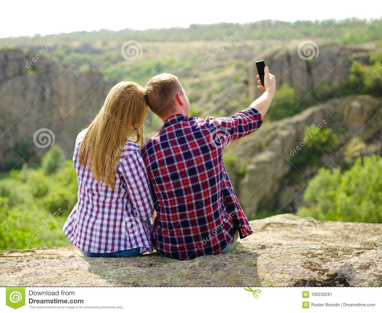 Active healthy and progressive couple relaxing on a camping trip in a national park and taking a selfie on a blurred natural background