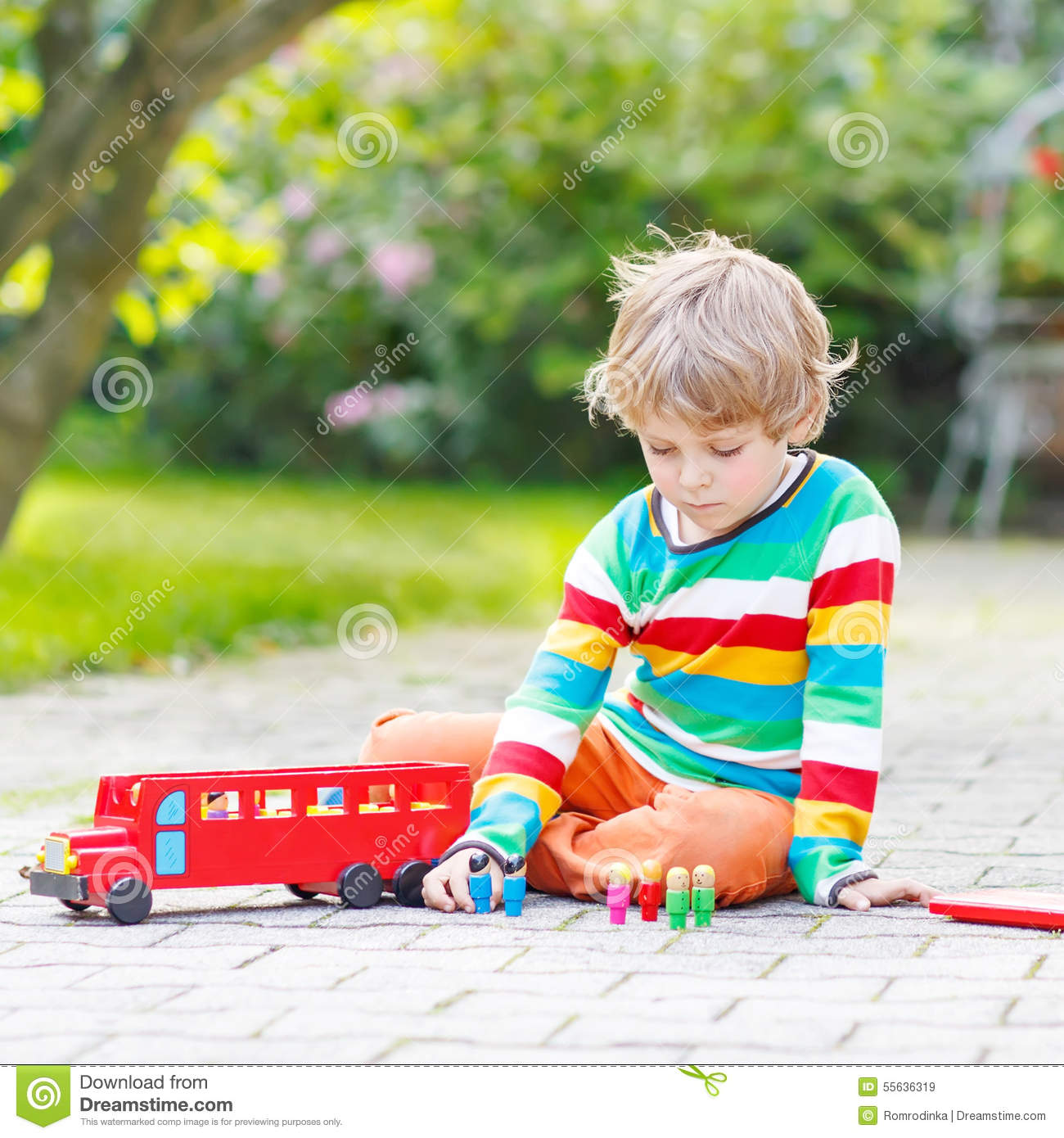 Toys For Active Boys : Active kid boy playing with red school bus and toys stock
