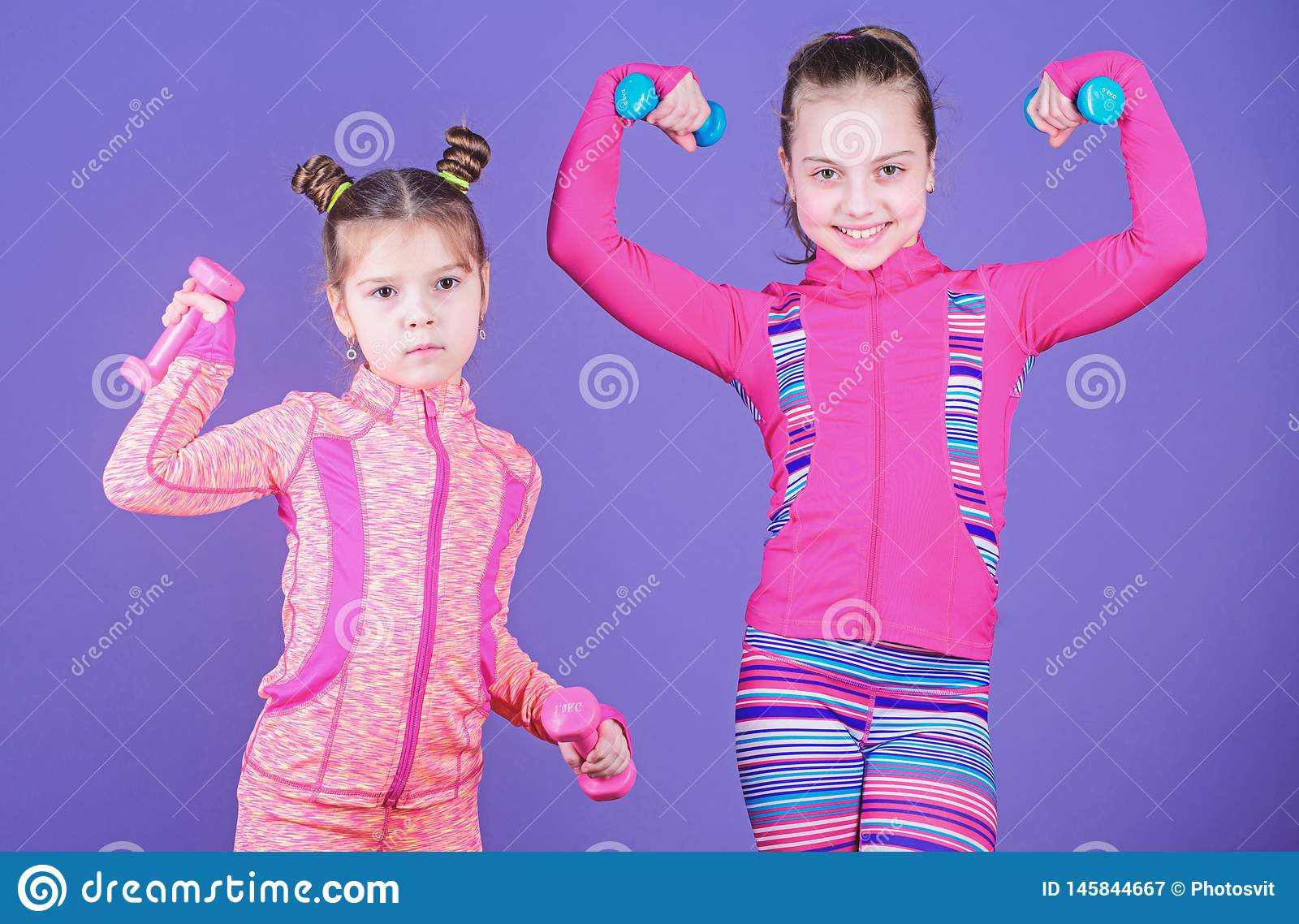 Active lifestyle. Sport and fitness for kids. Cute sisters doing gym fitness exercises with dumbbells. Little children