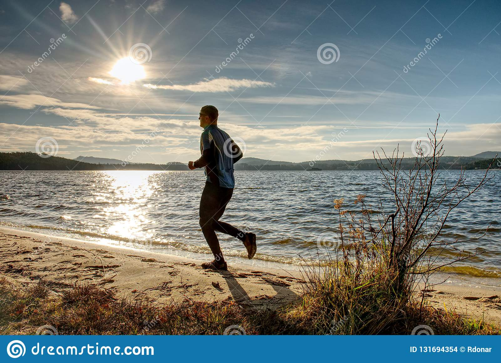 Active Man running at lake. Travel adventure healthy lifestyle concept vacations, athletic person