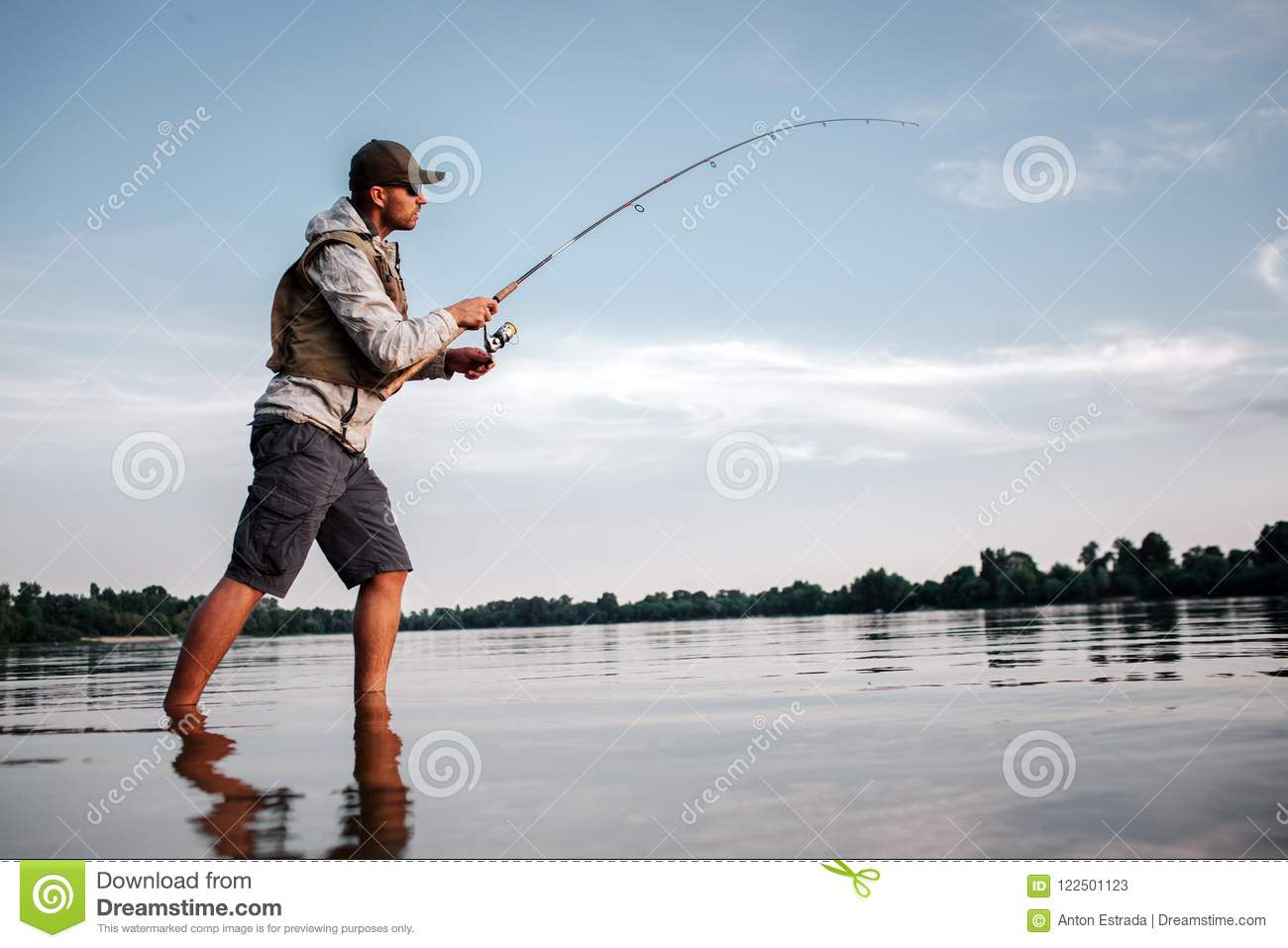 Active man is standing in shallow and fishing. He holds fly rod in hands. Man is twisting around reel to make spoon