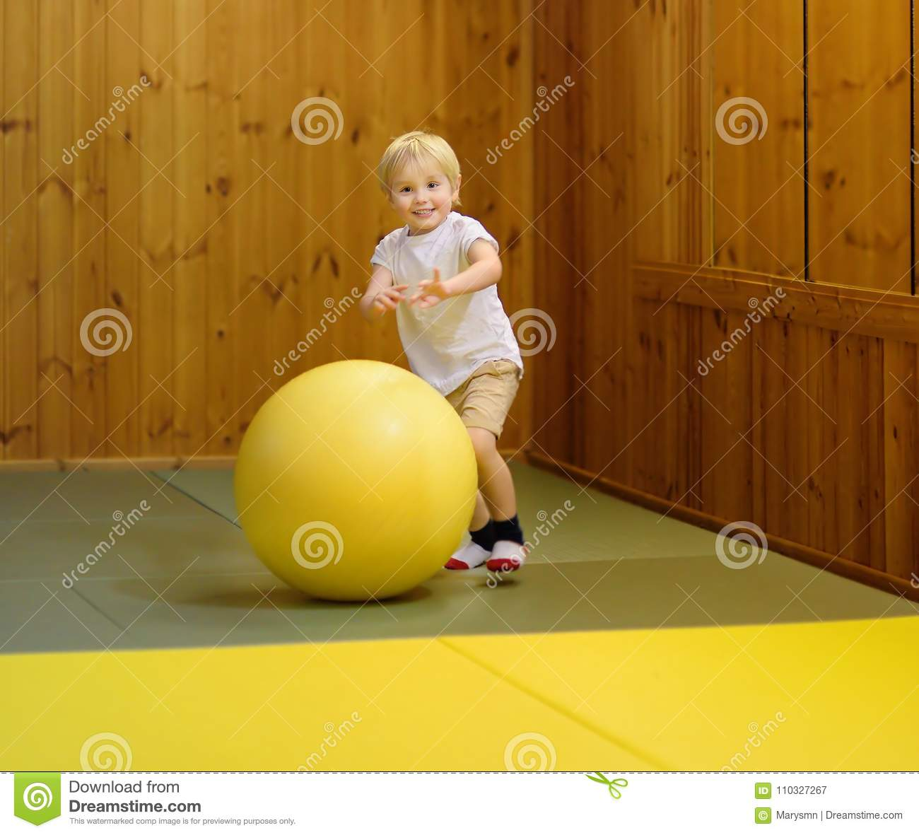Active preschool boy playing with big ball in indoor sports hall/gym class