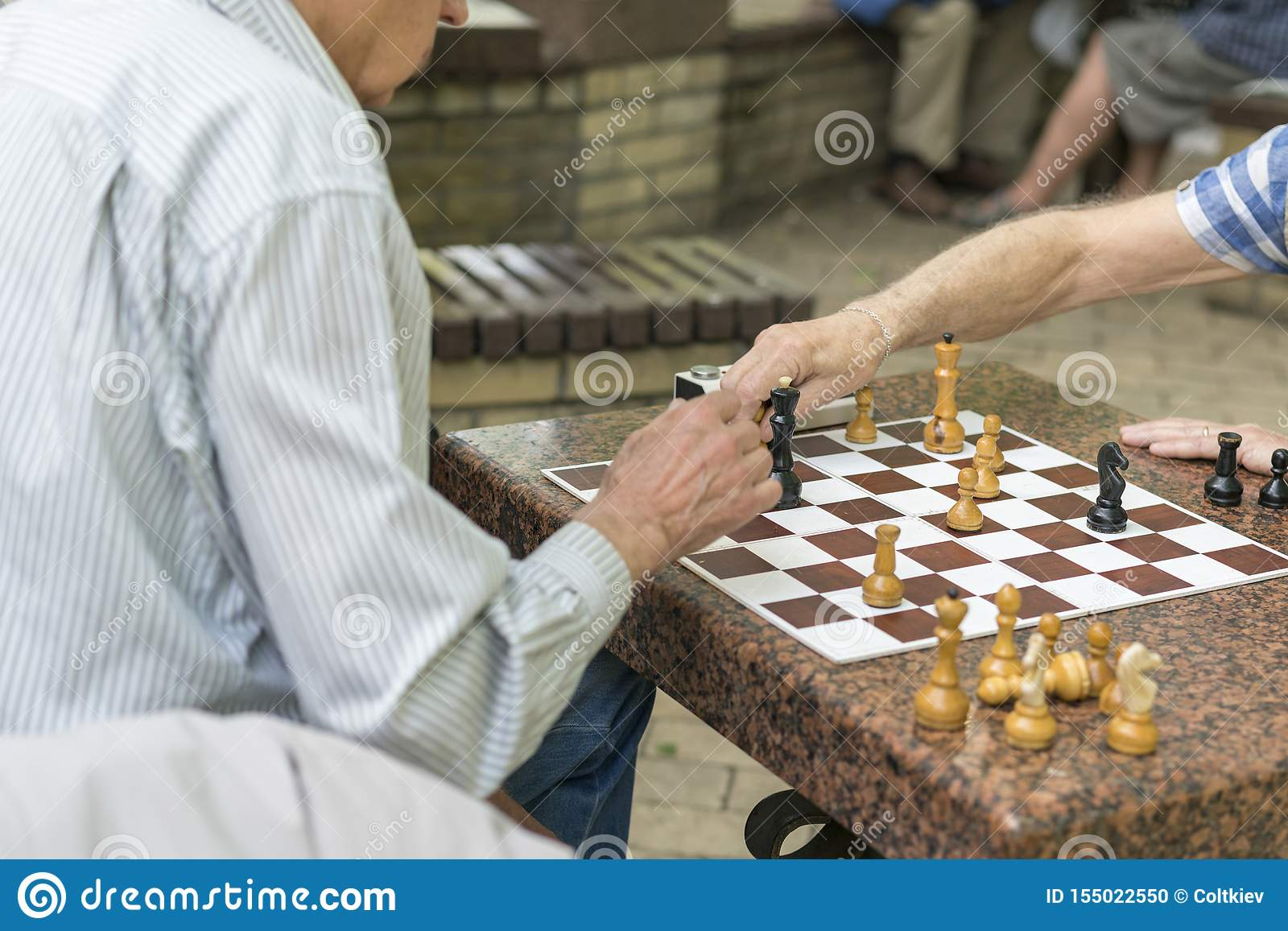 Active retired people, old friends and free time, seniors having fun and playing chess game at park. Waist up. Old men playing