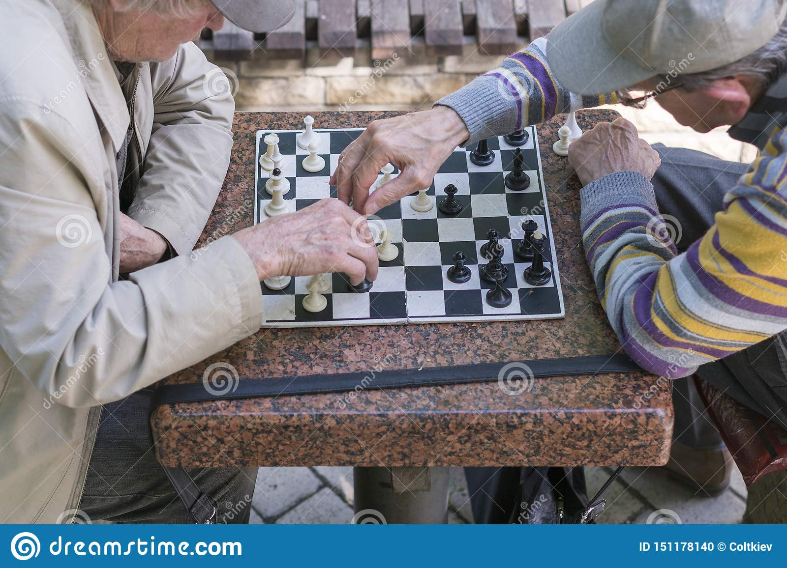 Active retired people, old friends and free time, two seniors having fun and playing chess game at park. Old men are playing chess