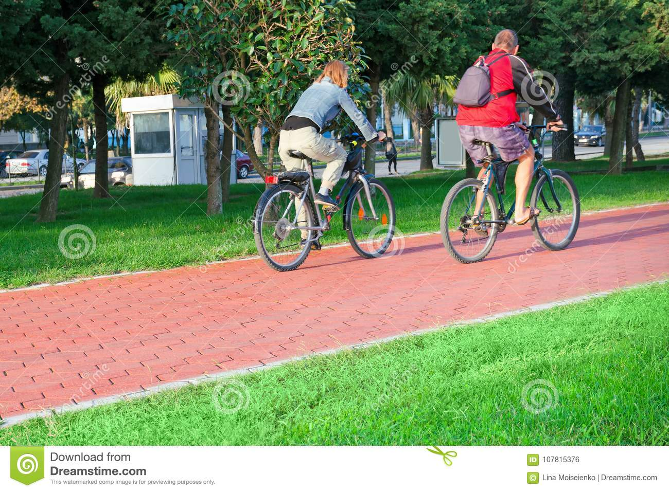 Active senior age and urban life - a couple of city dwellers a man and a woman at an age go on bicycles on the bike path.