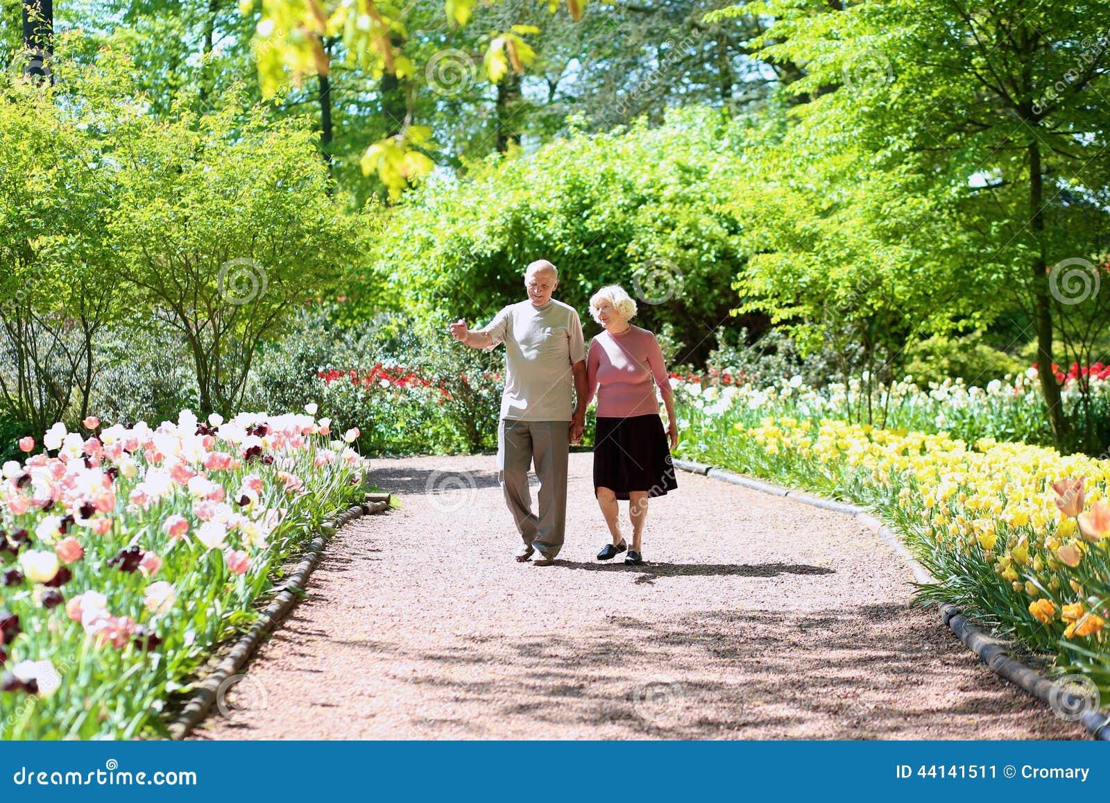 Active senior couple in beautiful flowers park