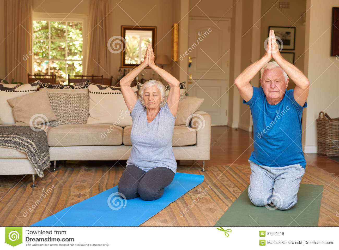 Active senior couple practising yoga together in their for Living room yoga
