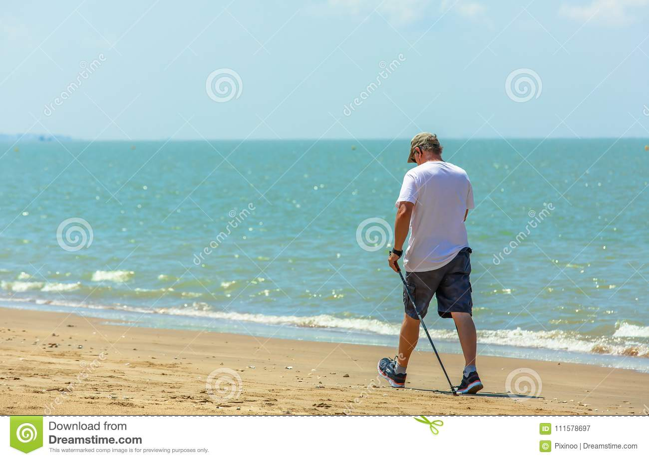 Active senior man walking with nordic walking poles on the beach