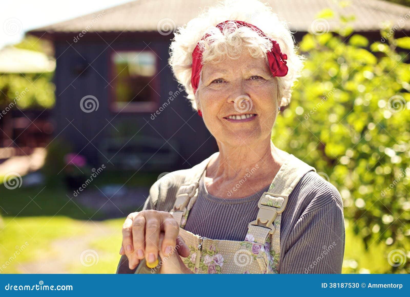 Active senior woman standing in backyard garden