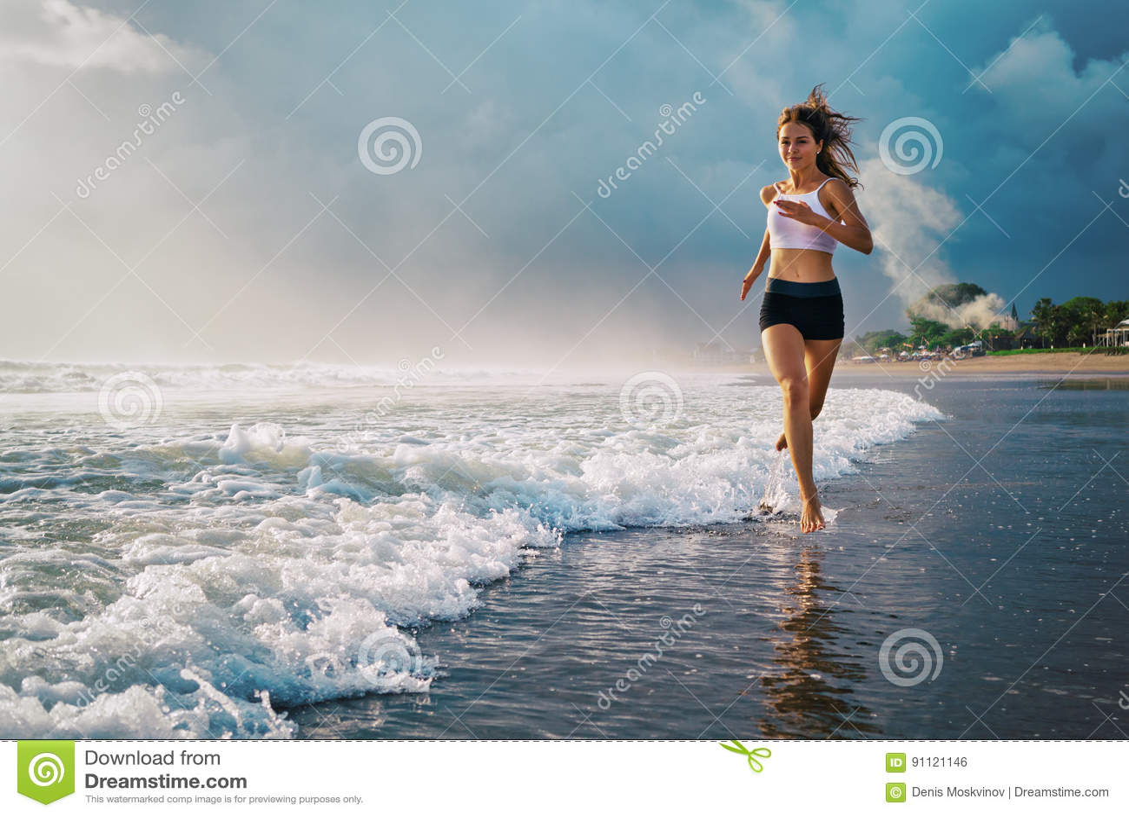 Active sporty woman run along sunset ocean beach. Sports background.