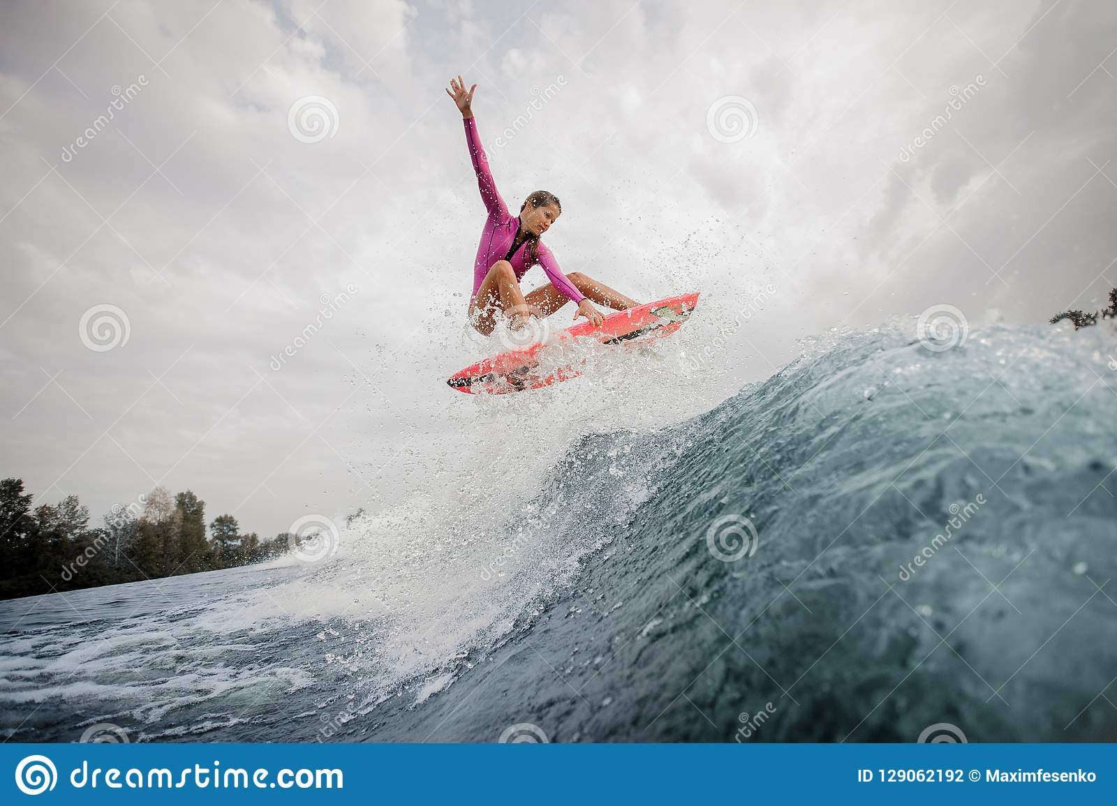 Active teenager girl in the pink swimsuit jumping on the orange