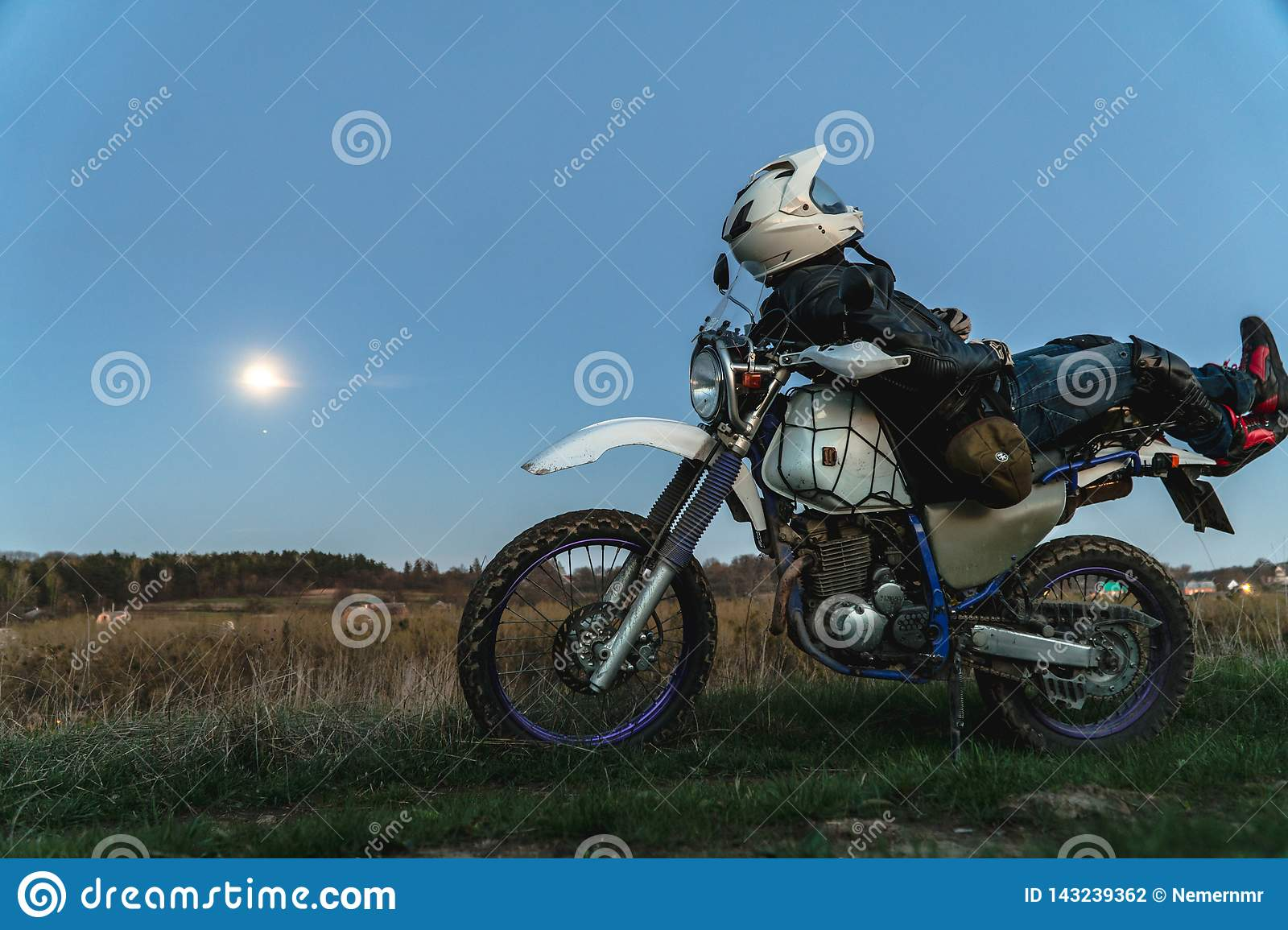 Active way of life, enduro motorcycle, a guy looks at the stars at night and the moon, unity with nature, the spirit of adventure
