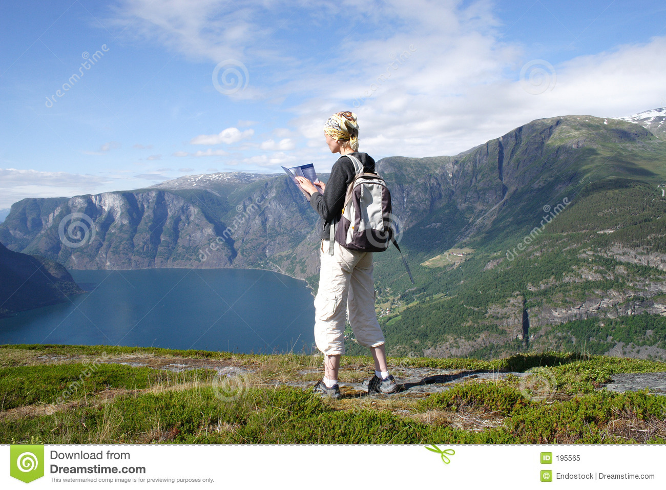 Active woman at the top of mountains over the lake royalty free stock