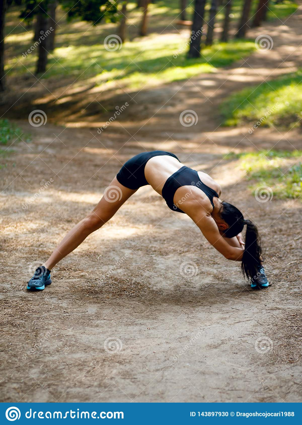 Active young woman workout outside, doing stretching exercises on legs and hands on the left side,  on park background