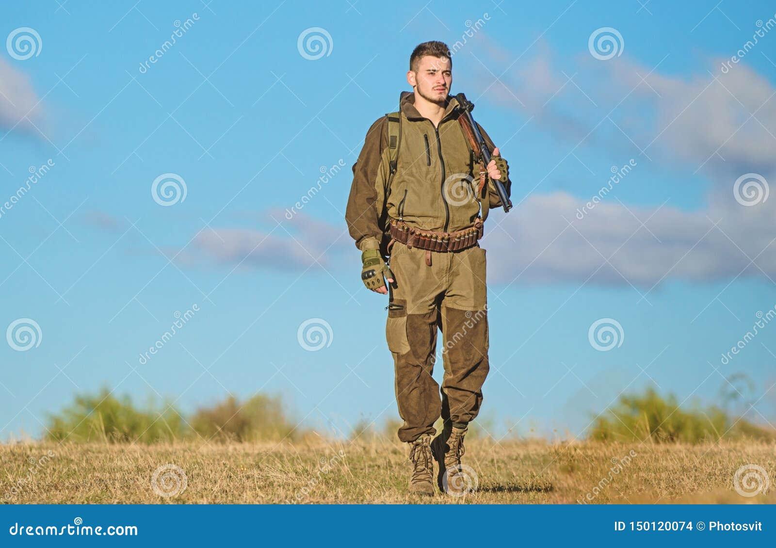 Actividad masculina de la afici?n El cazador del hombre lleva el fondo del cielo azul del rifle La experiencia y la pr?ctica pres