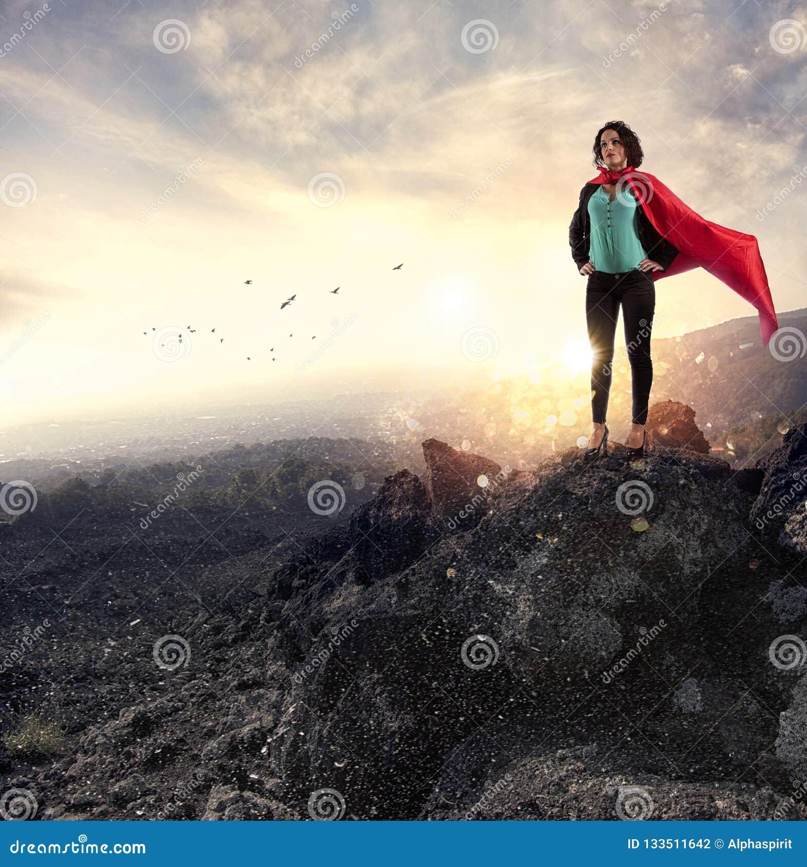 Actos acertados de la empresaria como un superhéroe en una montaña Concepto de determinación y de éxito
