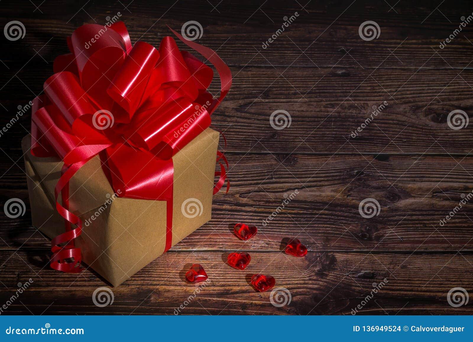 Actual caja con la cinta roja del arco y jugar a hockey shinny los pequeños corazones para día de San Valentín