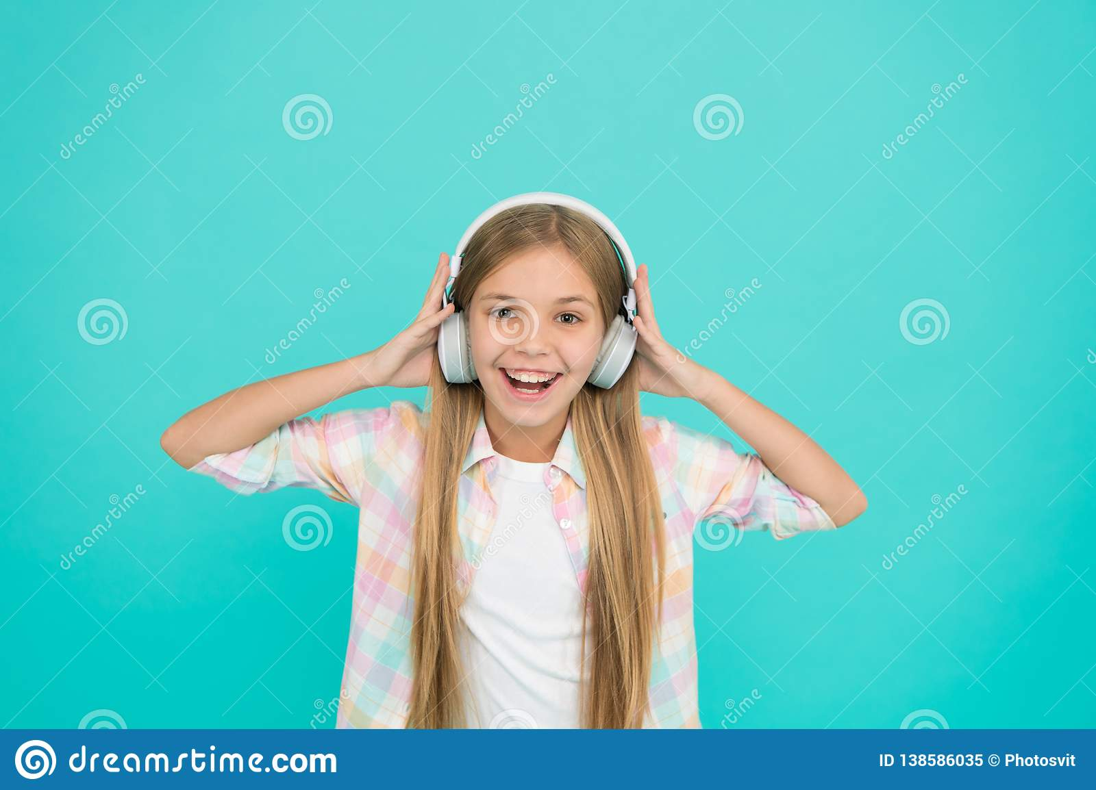 She is actually a big music fan. Happy little child enjoy music playing in headphones. Little girl child listening to