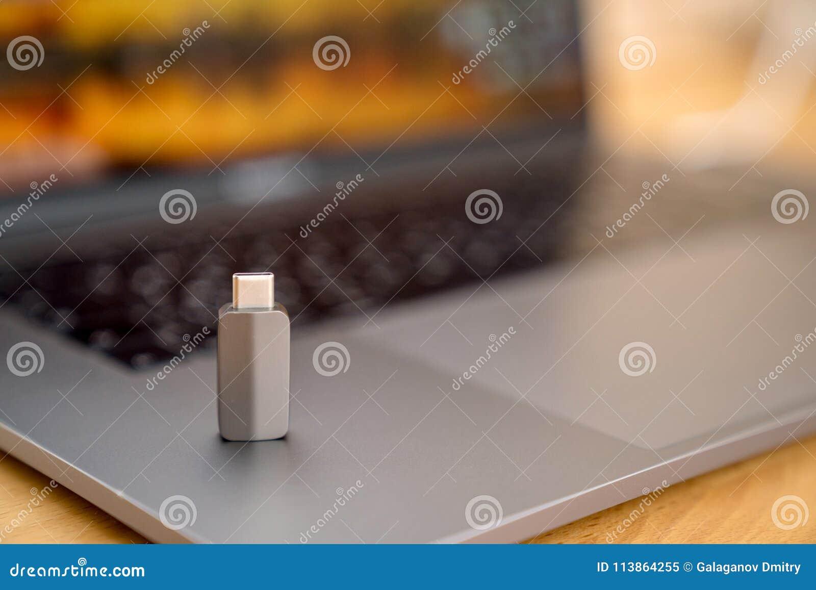 Adaptateur de Gray Thunderbolt USB-C sur le clavier gris sur le fond d ordinateur portable