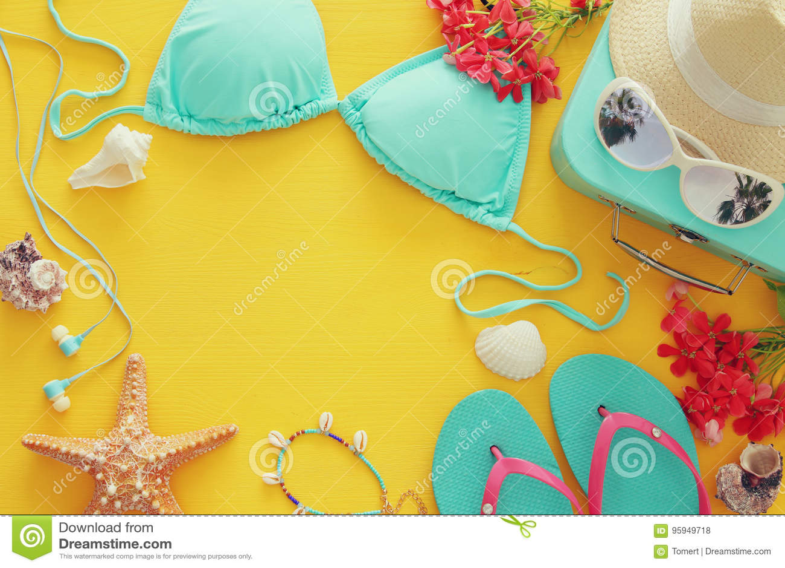 Adatti il bikini femminile del costume da bagno su fondo di legno giallo Concetto di vacanza della spiaggia di estate