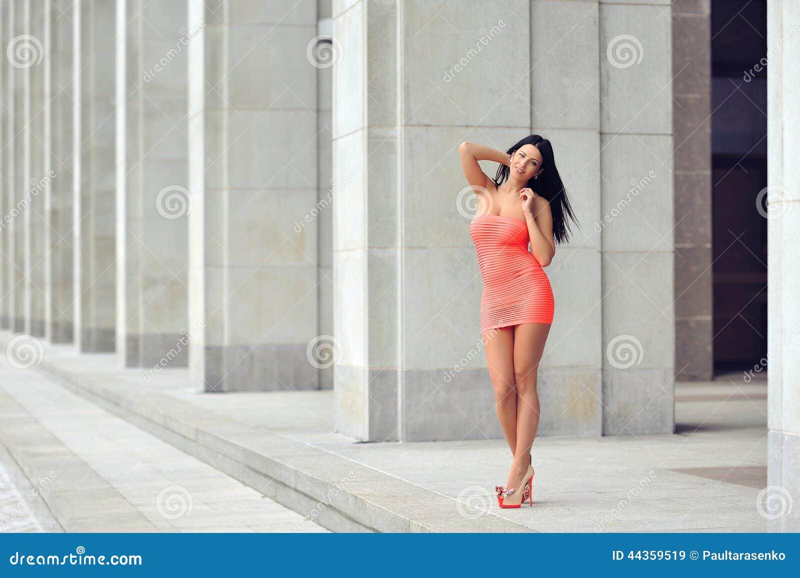 Adatti il ritratto di bella donna in vestito rosso che posa nella c