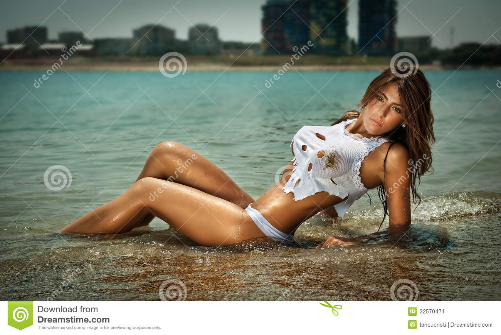 Adatti il ritratto di giovane ragazza castana sexy in bikini e maglietta bagnata alla spiaggia