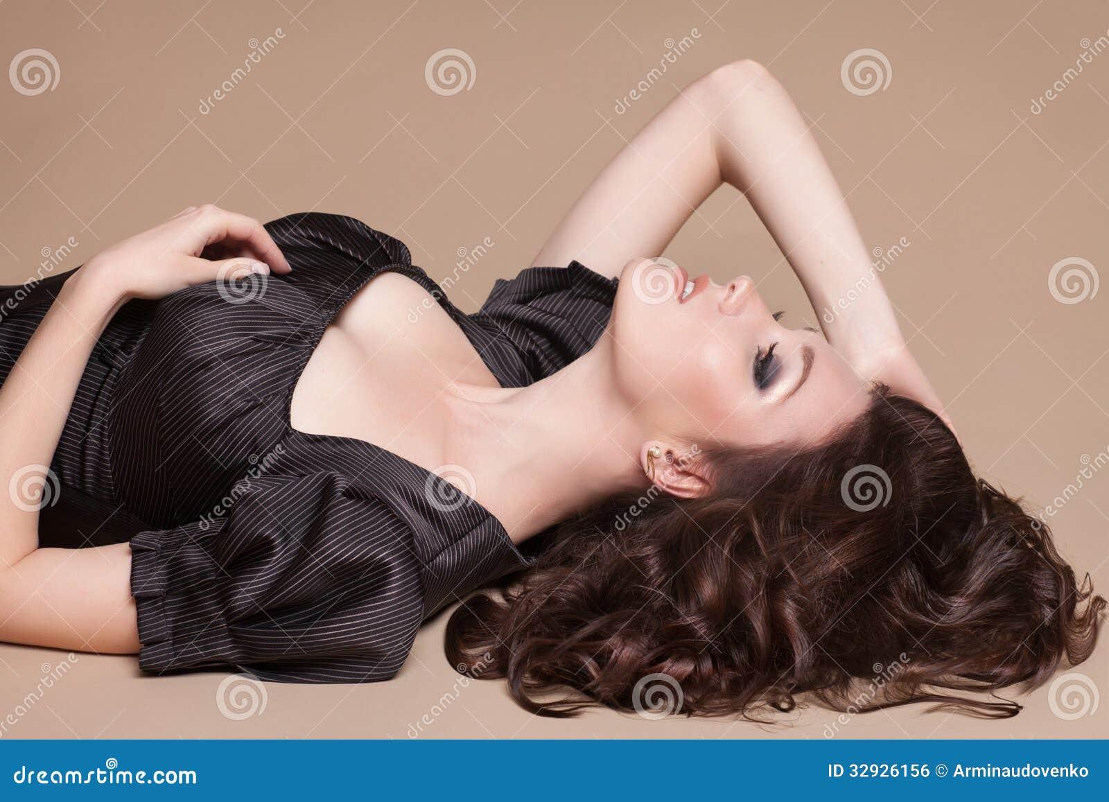 Adatti la donna castana con la ragazza marrone dei capelli ricci con pelle perfetta e trucco. Retro di modello di bellezza