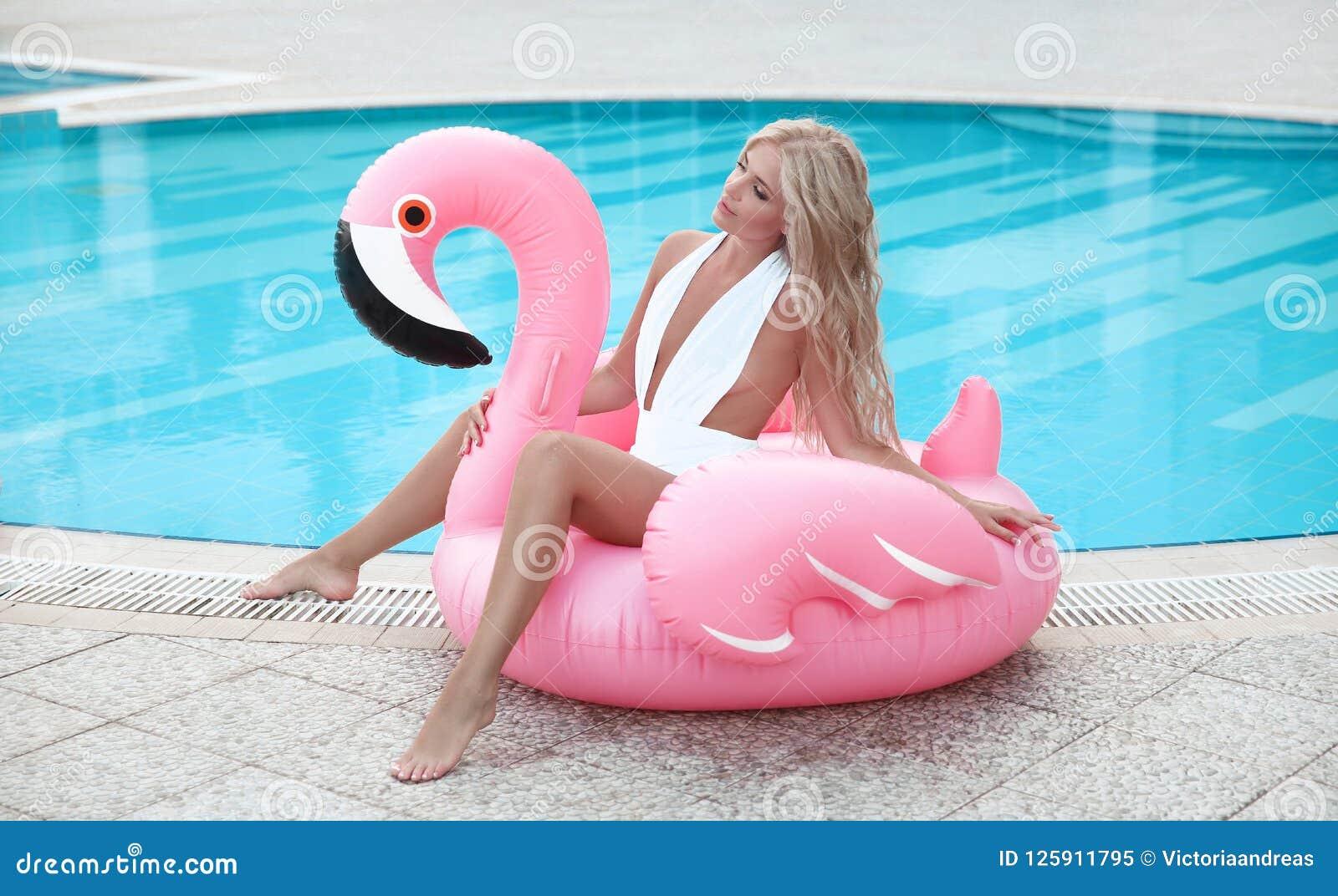 Adatti la donna di modello bionda sexy in bikini bianco che posa sul rosa dentro