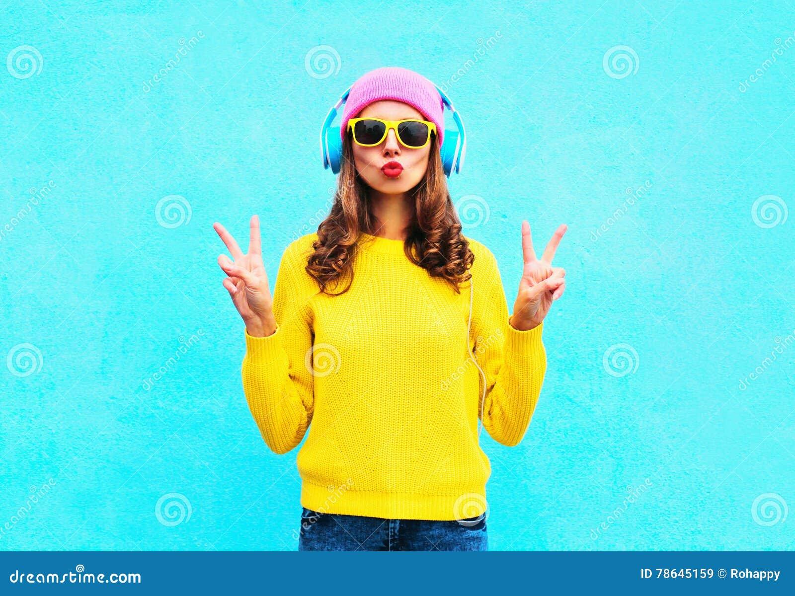 Adatti la ragazza abbastanza fresca in cuffie che ascolta la musica che porta gli occhiali da sole rosa variopinti ed il maglione
