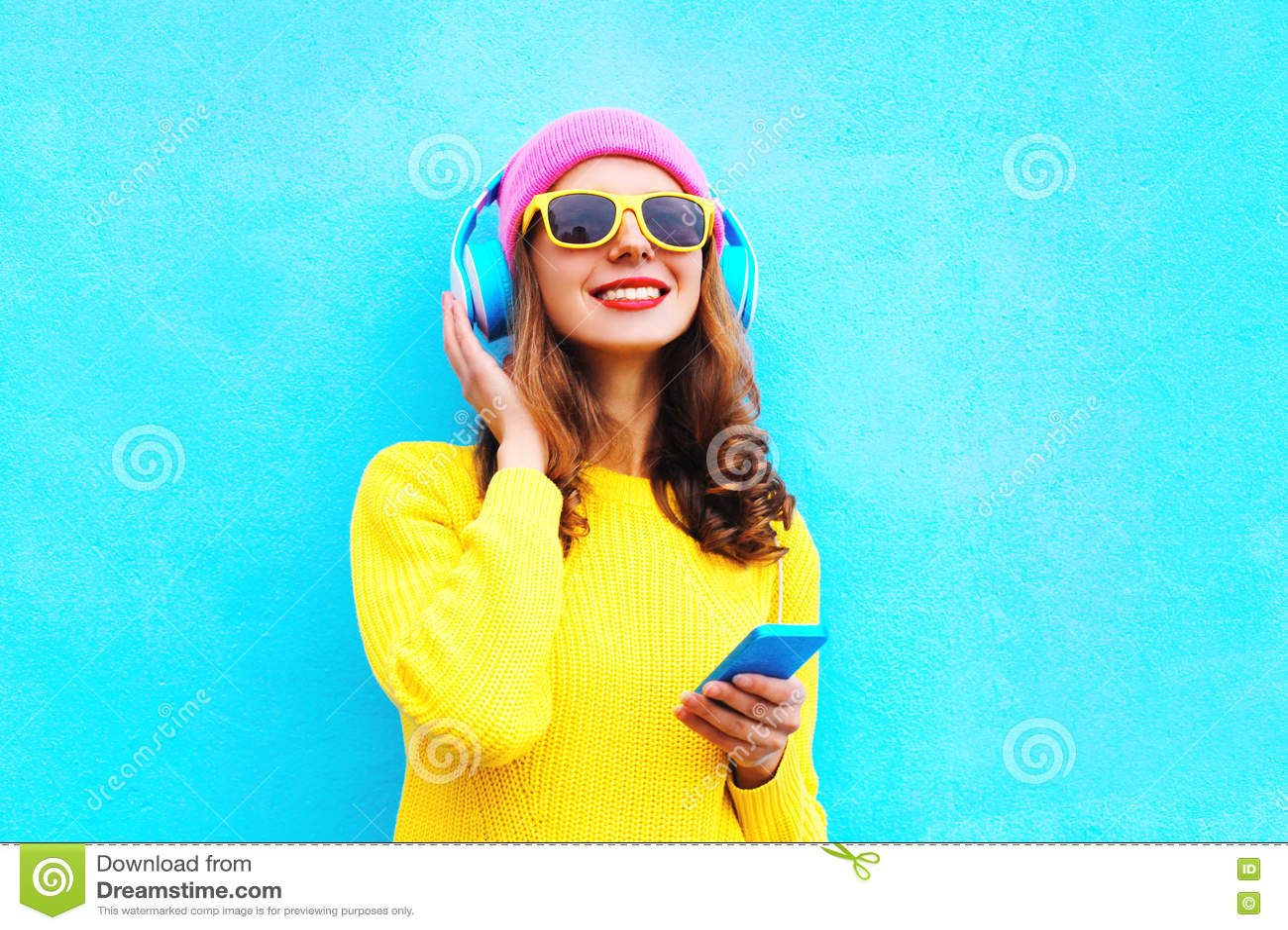 Adatti la ragazza spensierata abbastanza dolce che ascolta la musica in cuffie con lo smartphone che indossa gli occhiali da sole