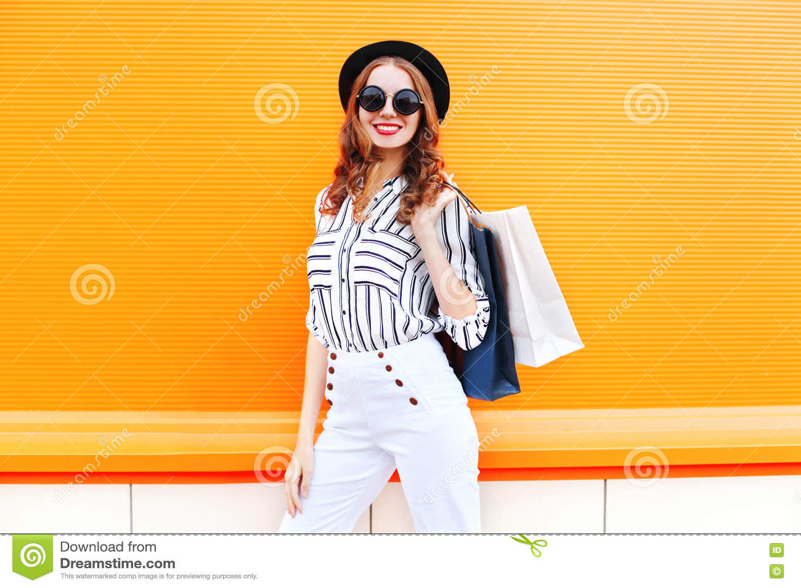 Adatti a modello sorridente abbastanza giovane della donna con l uso dei sacchetti della spesa i pantaloni bianchi black hat sopr