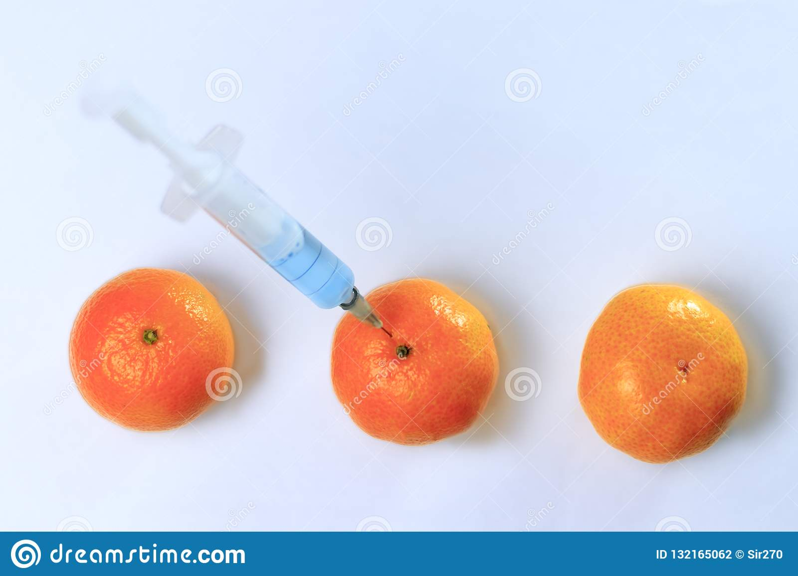 Added mandarin with a syringe. The background is white but not isolate, in the syringe is blue liquid. Chemical experiments in the