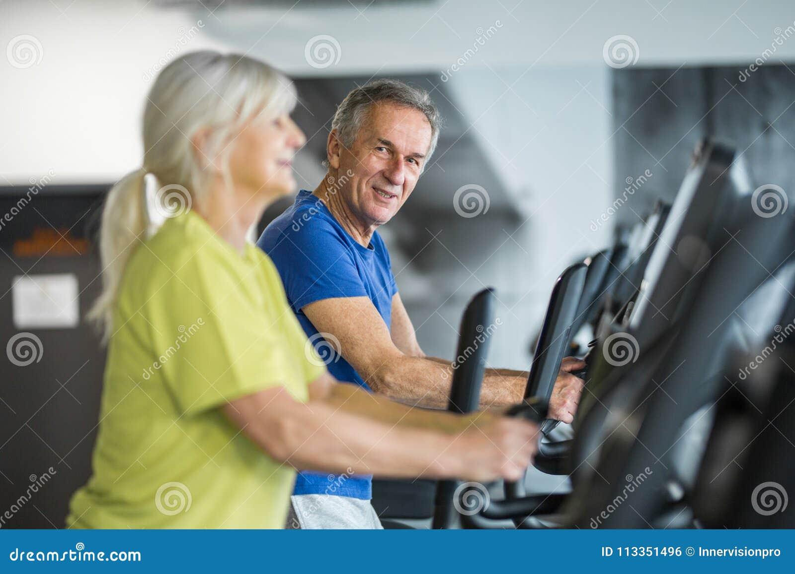Addestramento senior felice delle coppie sulla scala passo passo alla palestra