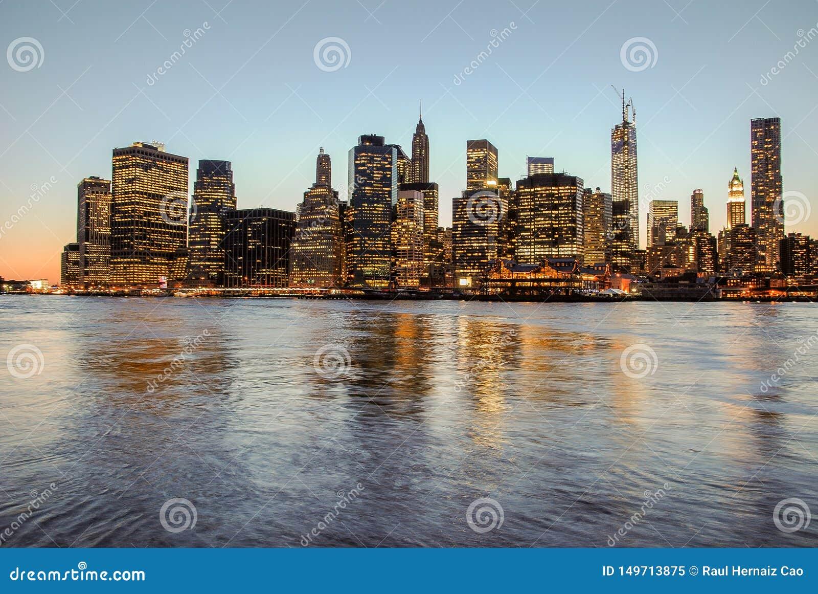 Adembenemende die mening van horizon van Manhattan bij zonsondergang, aan nacht wordt gesloten De mening van Nice sinds Brooklyn