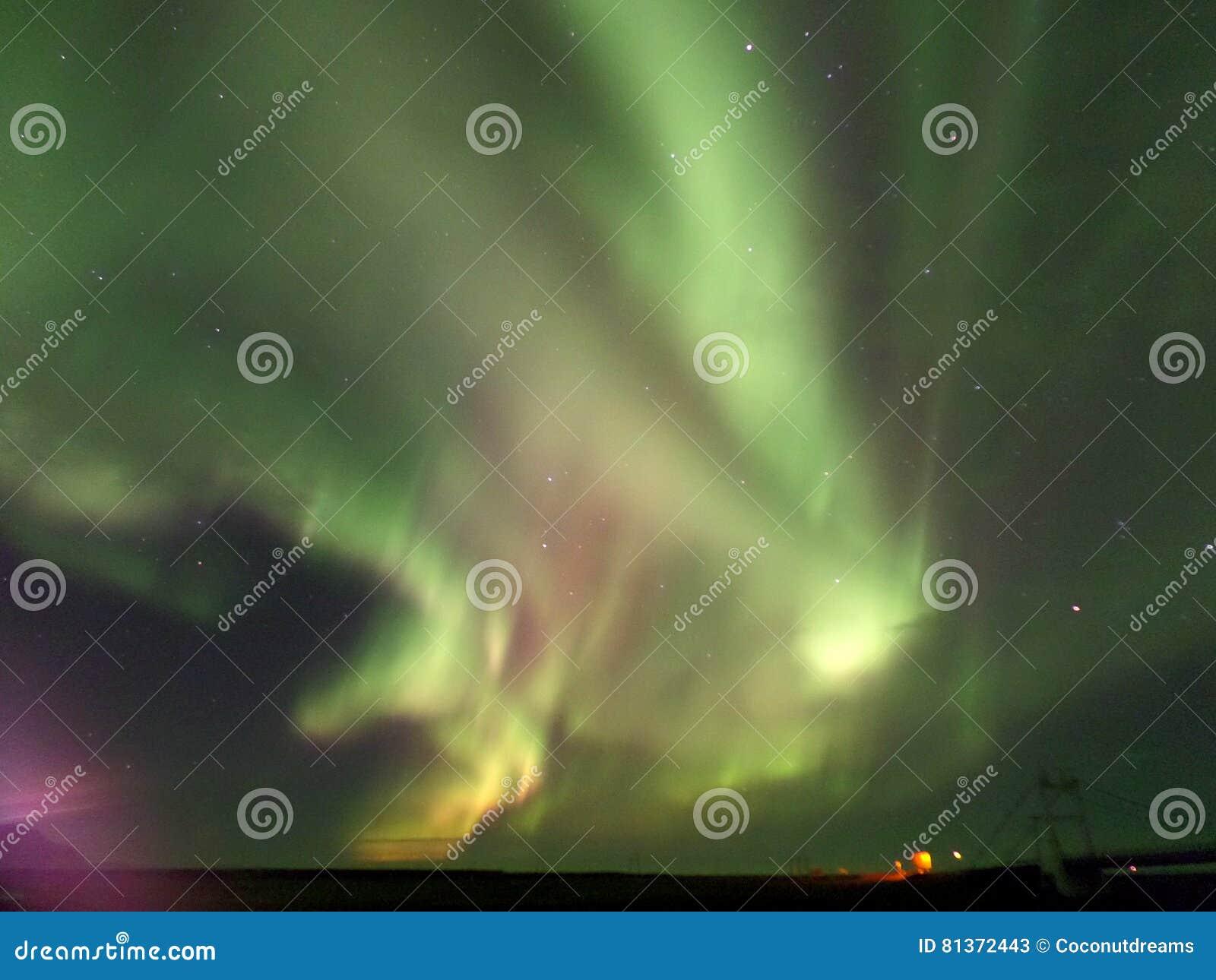 Adembenemende groene en roze Aurora Borealis die op de nachthemel opvlammen