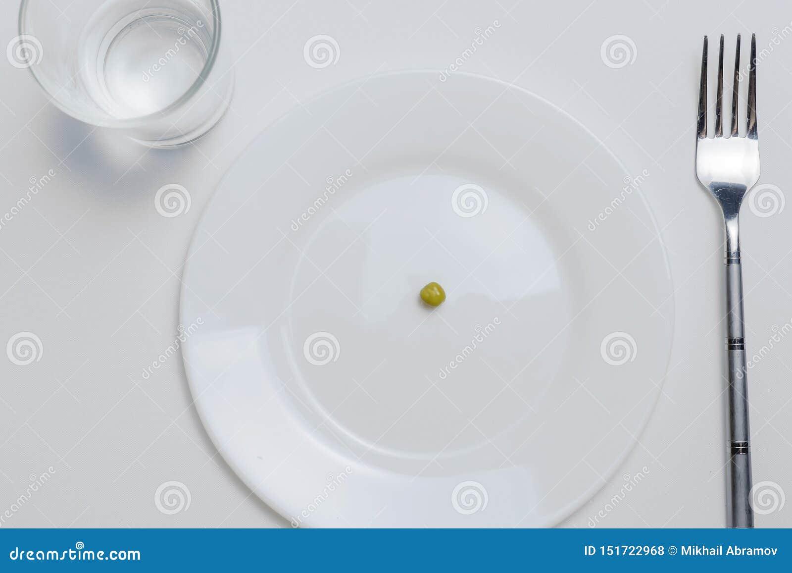 Adiete el concepto un guisante en una placa blanca vacía con la bifurcación