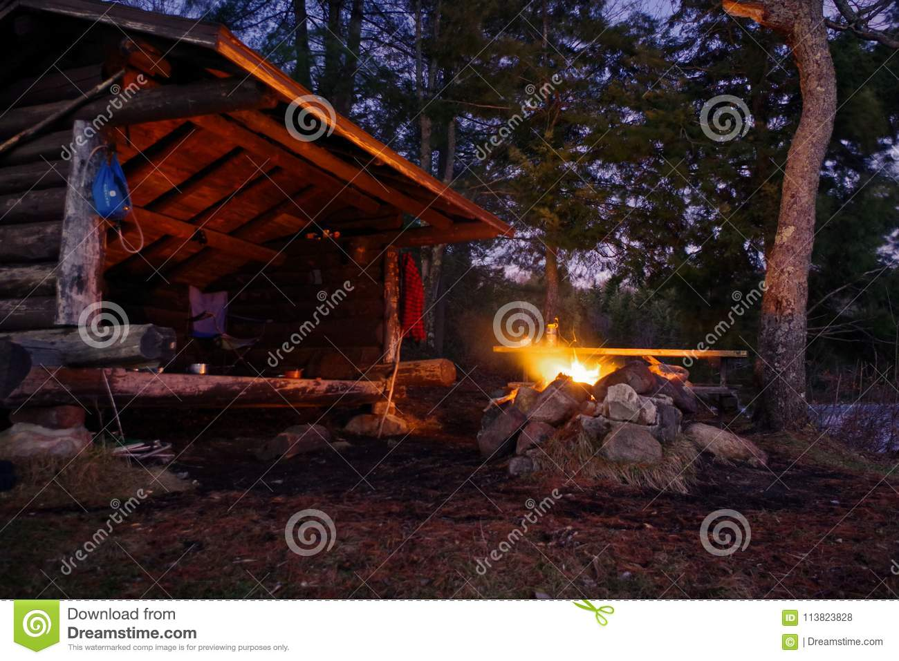 Adirondack Lean to Bushcraft camp shelter with fire at night in the mountains.