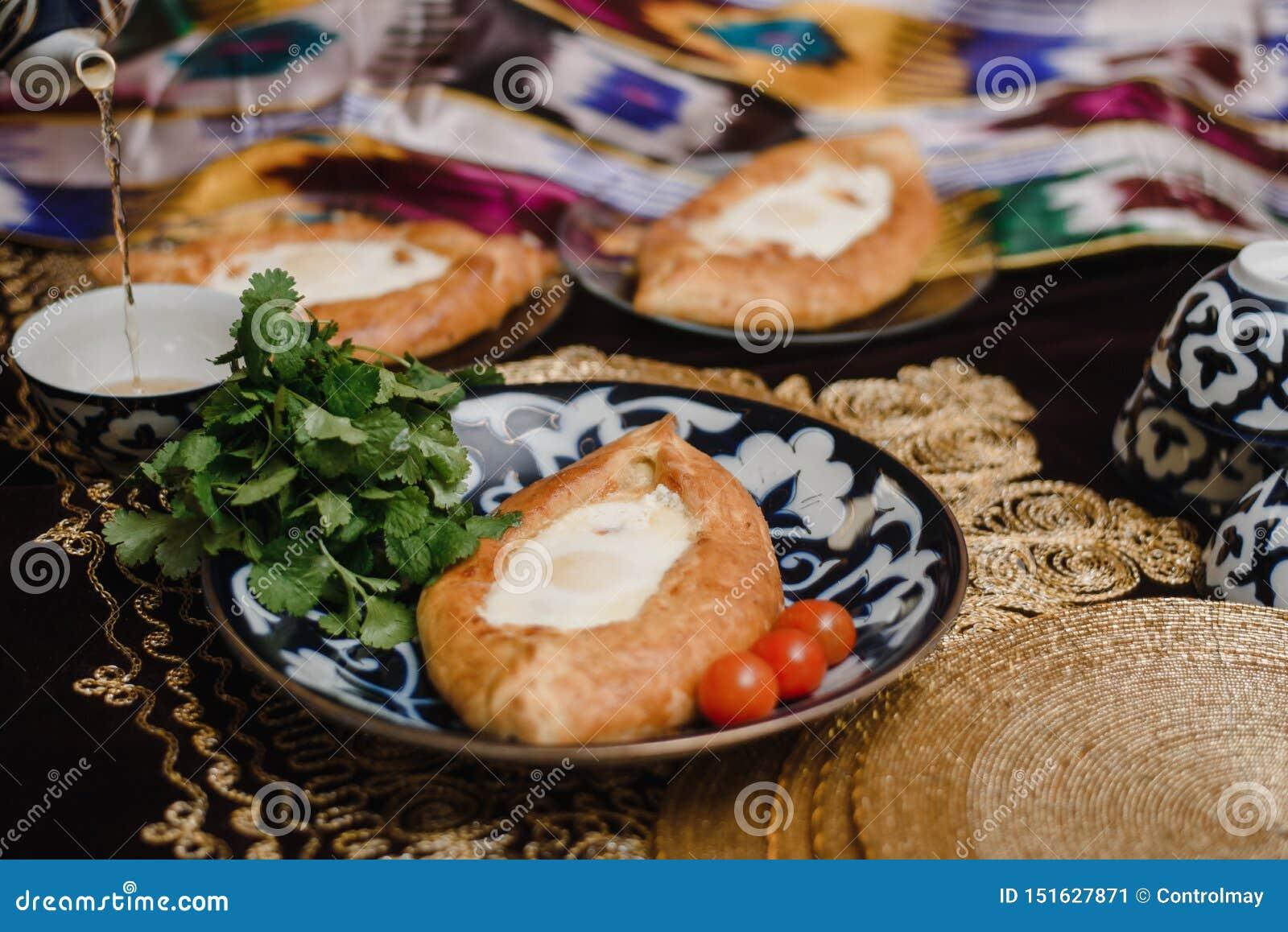 Adjara khachapuri on the eastern table. egg in hot bread on oriental plates is in a restaurant
