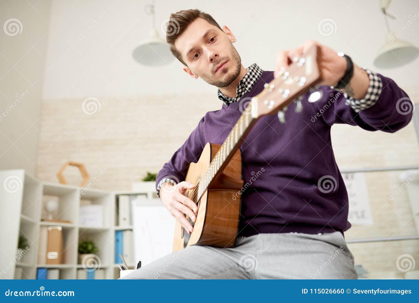 Adjusting Guitar at Modern Office