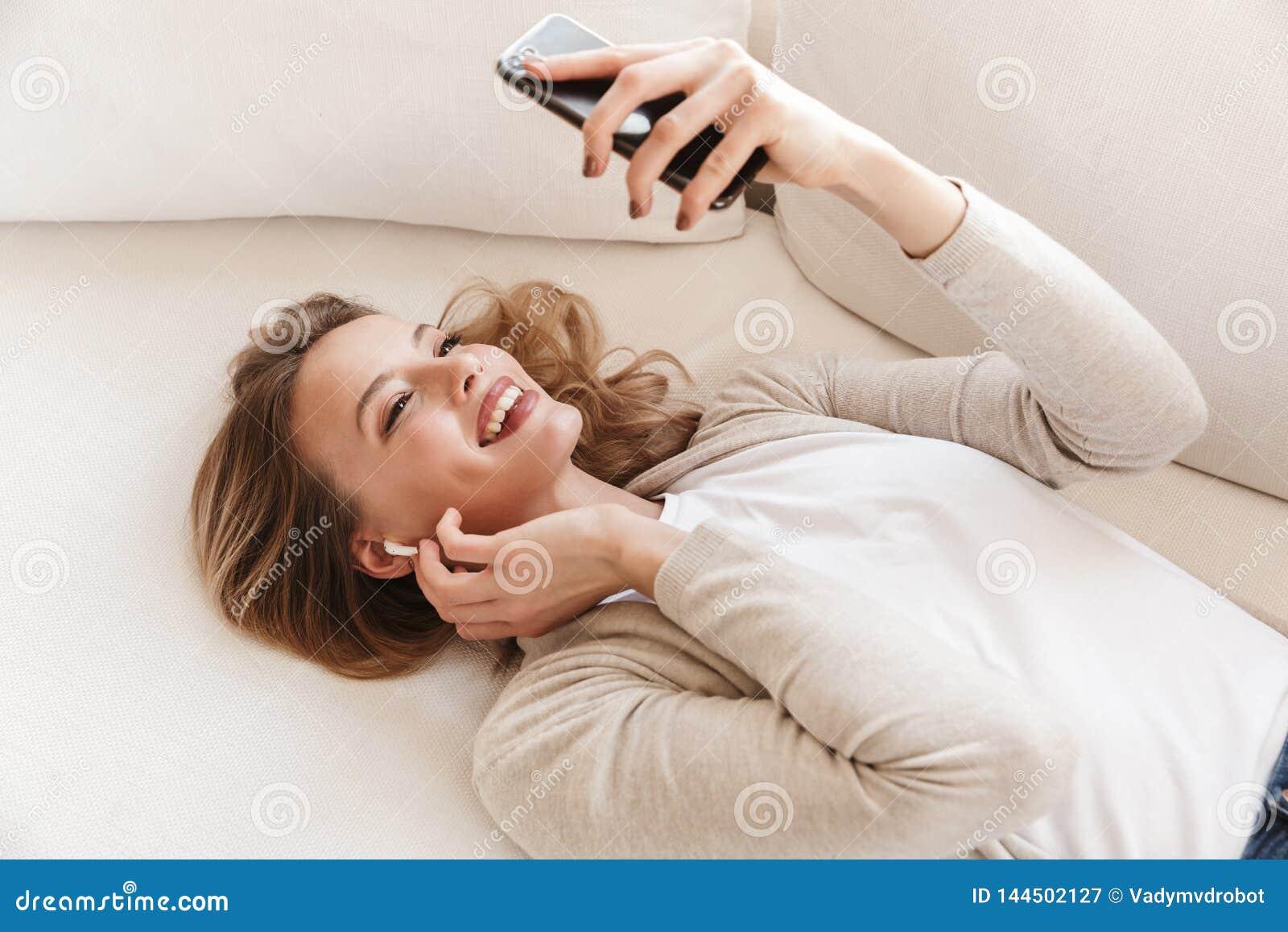 ?adna blondynki kobieta pozuje siedzie? indoors w domu s?uchaj?cy muzyk? z s?uchawkami