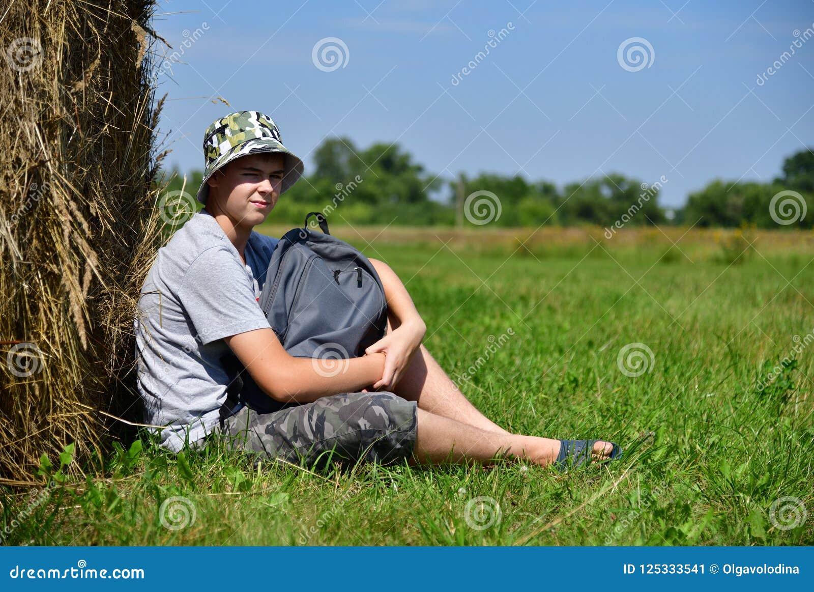 Adolescent avec le sac à dos se reposant à côté de la pile de paille