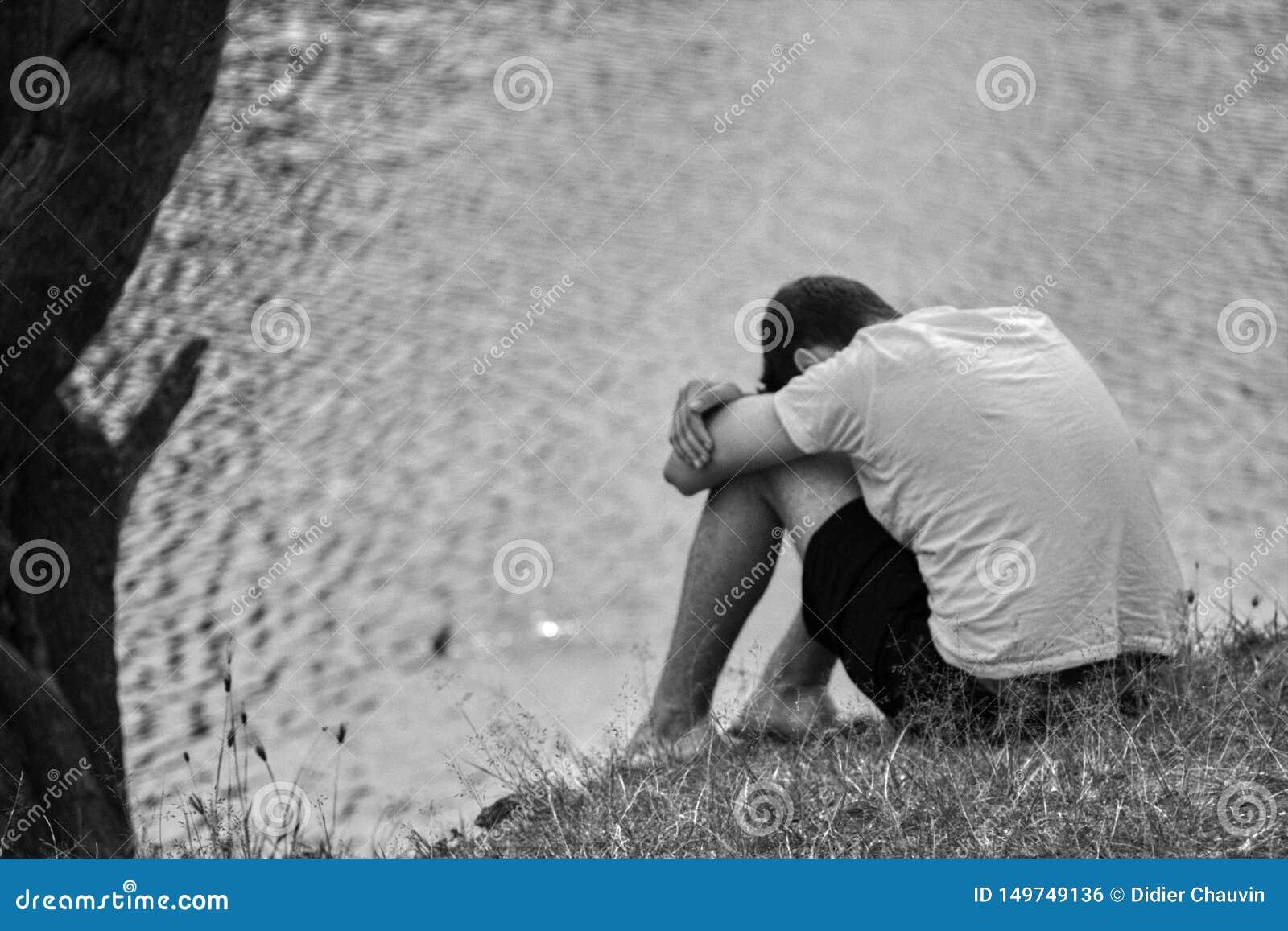 Adolescent déprimé s asseyant devant l eau