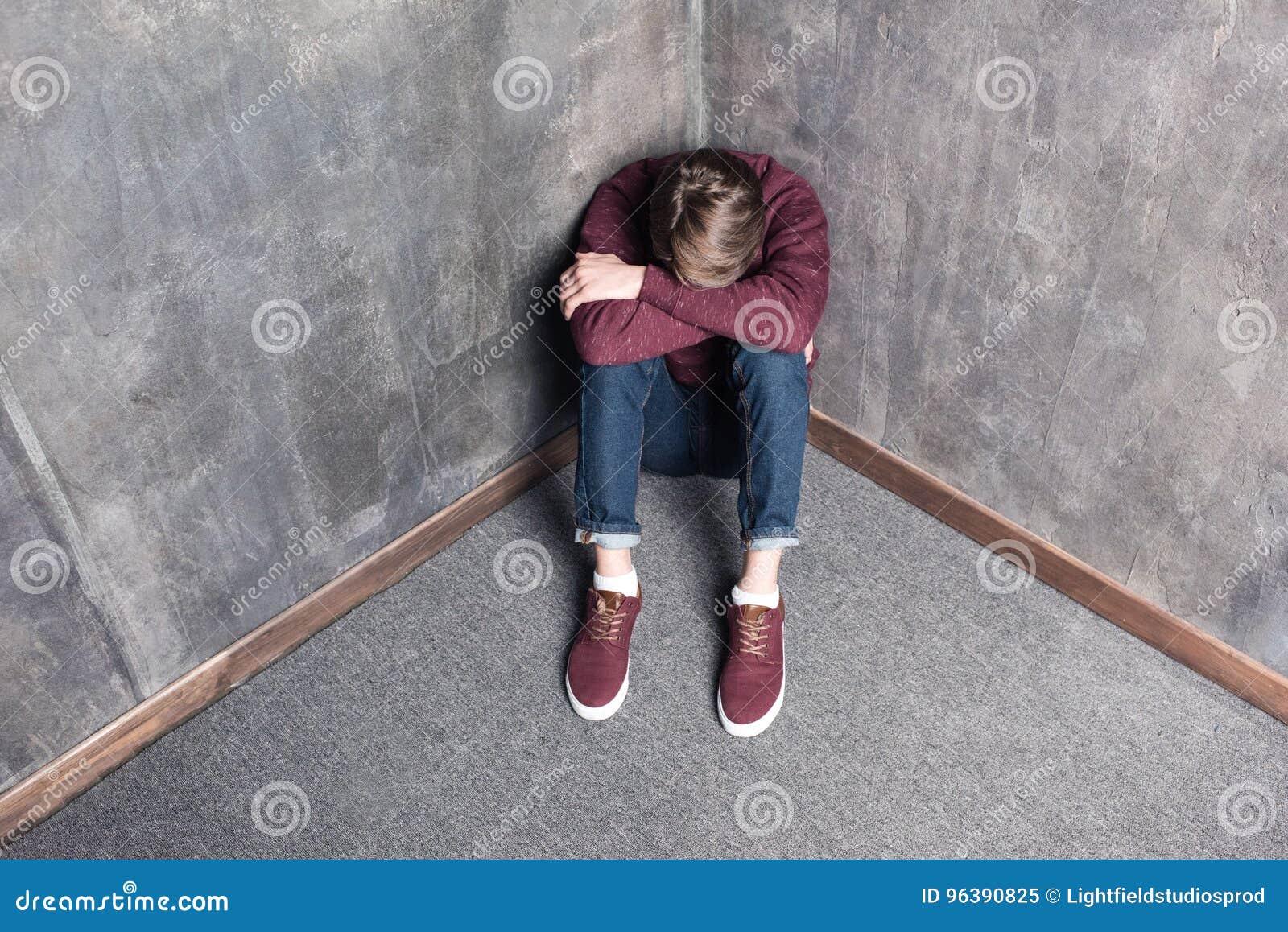 Adolescent déprimé s asseyant sur le plancher