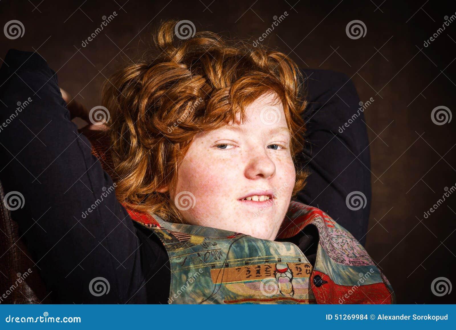 Adolescent expressif roux s asseyant dans le fauteuil