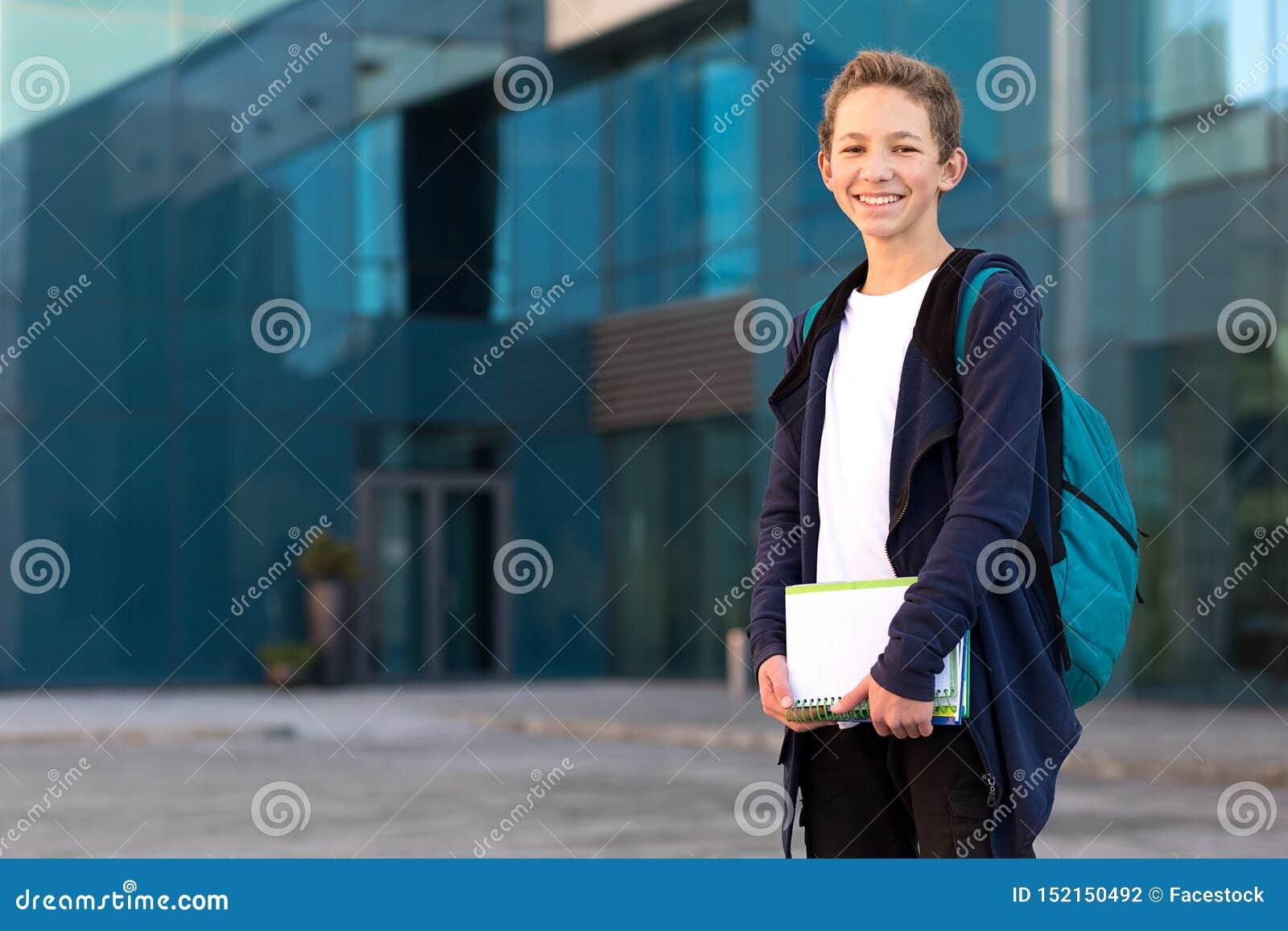 Adolescent extérieur avec les livres et le sac à dos