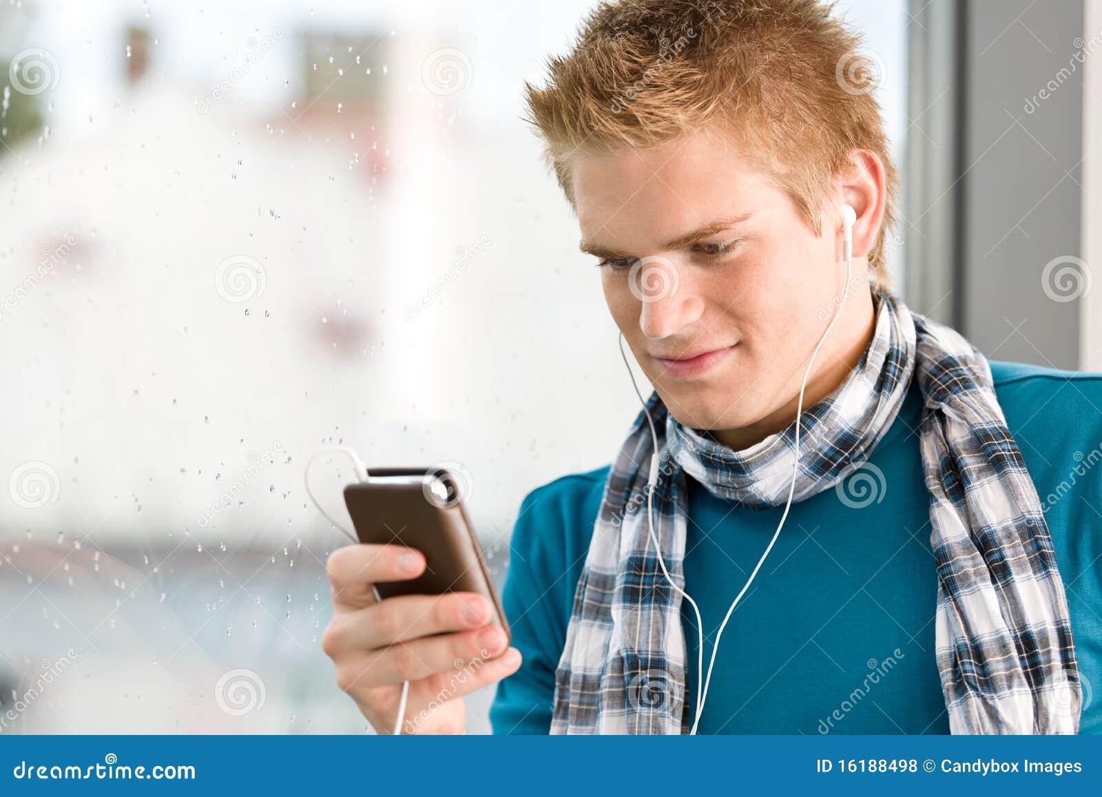Adolescent mâle avec le joueur mp3 et les earbuds