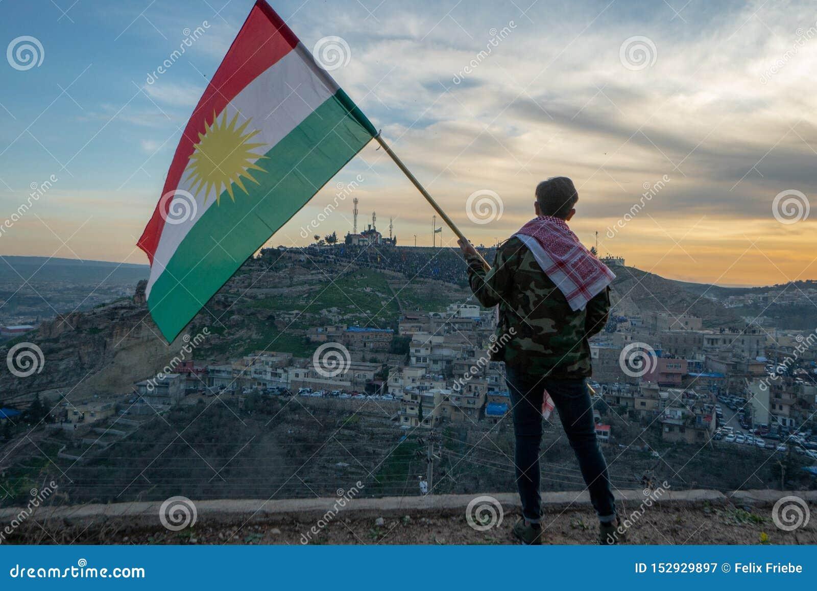 Adolescent tenant le drapeau du Kurdistan dans le nord de l Irak au temps de coucher du soleil