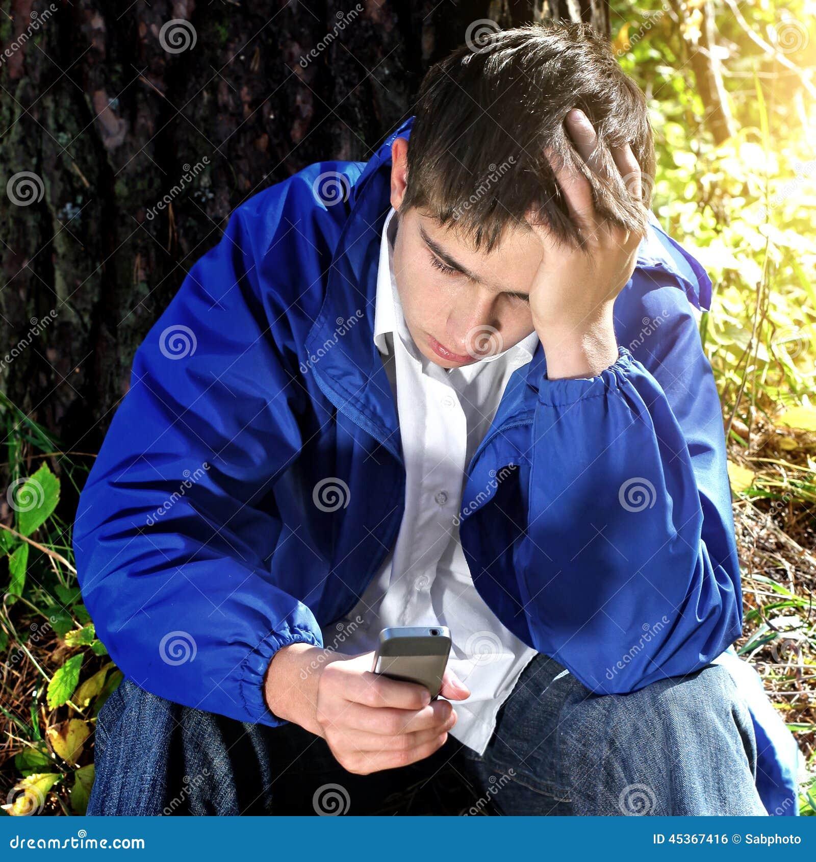 Adolescent triste avec le téléphone portable