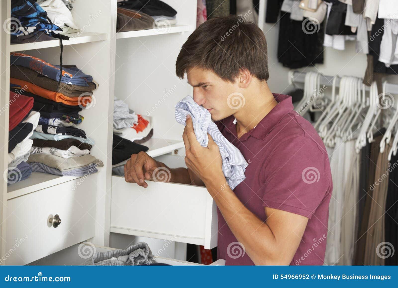 Adolescent vérifiant la fraîcheur des vêtements dans la garde-robe