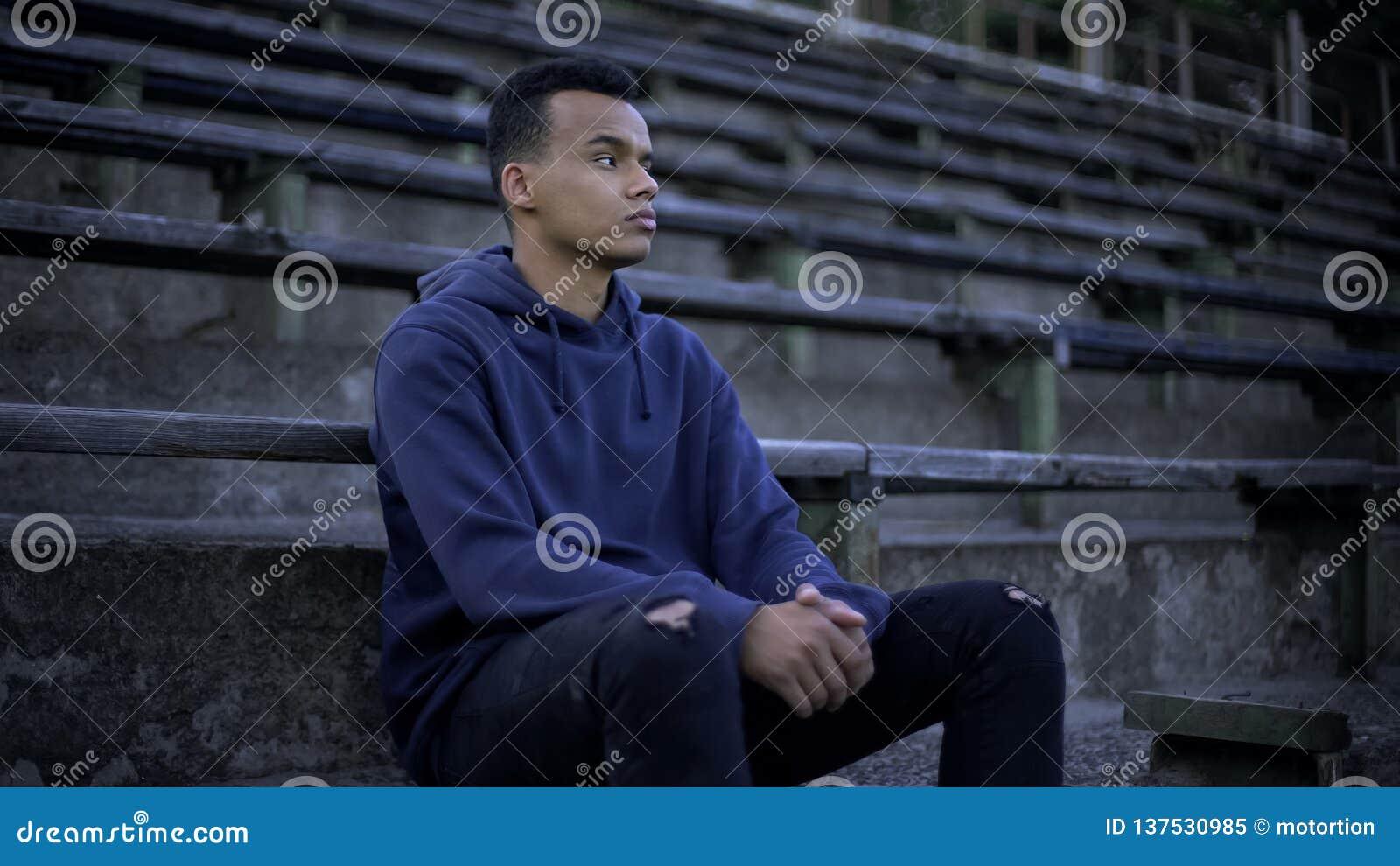 Adolescente afro-americano triste que senta-se na tribuna, na devastação e na pobreza ao redor